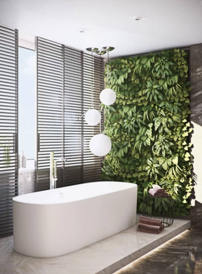 Modern bathroom with a garden wall design next to the bathtub.