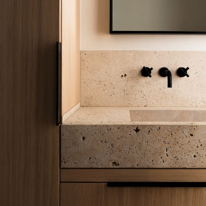 Stone bathroom sink on a wood vanity, great example of biophilic design.