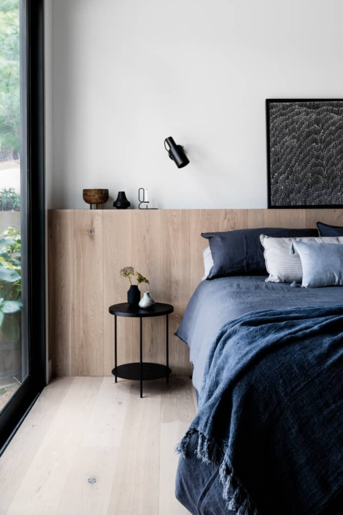 Minimalist bedroom with big window, great example of biophilic design.