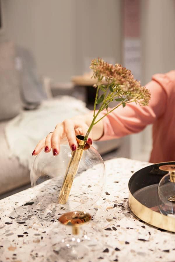 Me admiring a gold minimalist vase at Bolia.