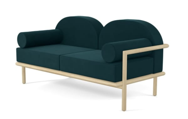 Sculptural sofa with curved back and cushions.