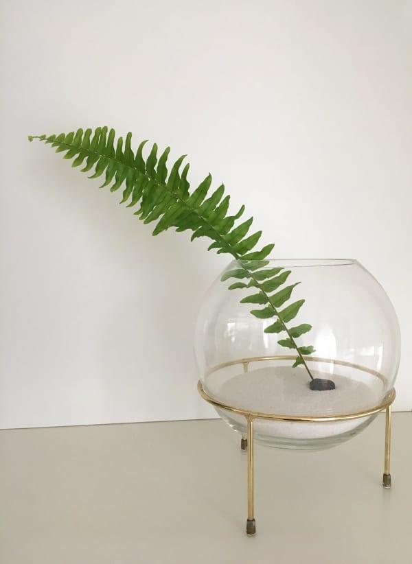 Minimal sculptural vase with a single-leaf arrangement.
