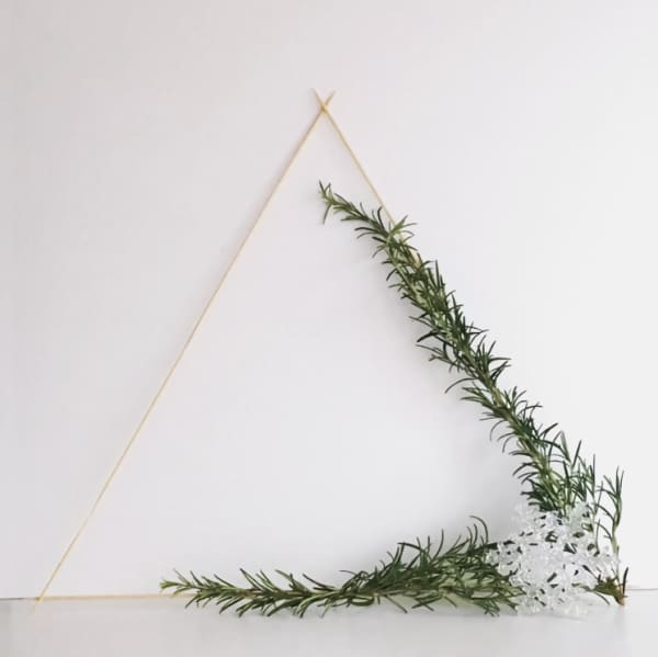 Triangular wooden wreath decorated with rosemary twigs.