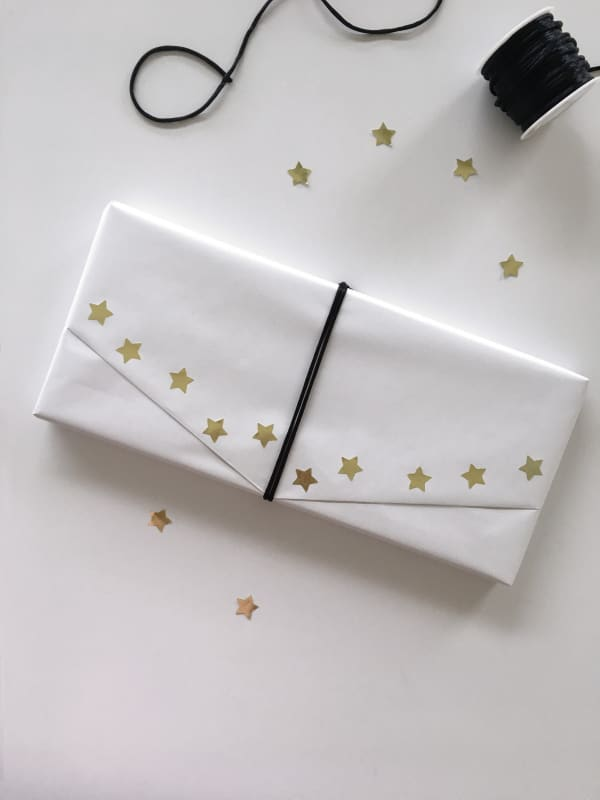 Gift wrapped in ordinary white paper and decorated with a ribbon and golden paper stars as an example of sustainable gift wrapping.