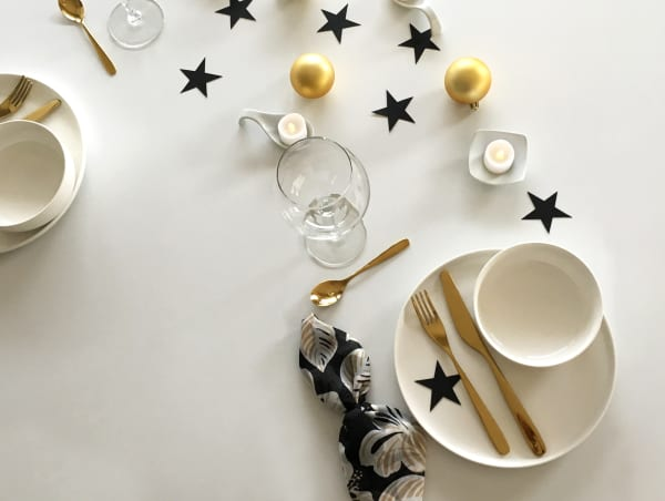 View of the same minimal modern Christmas table setting with two places arranged on consecutive sides of the table.