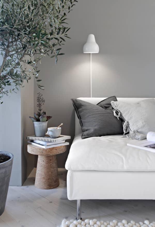 Sofa with soft cushions, a tea and few plants.