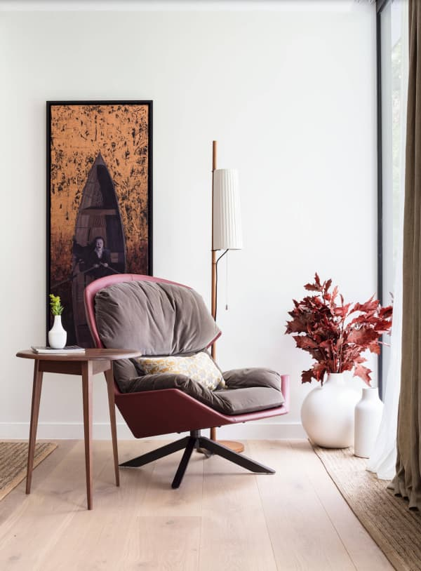 Relaxing armchair corner with branches of red leaves in a vase.