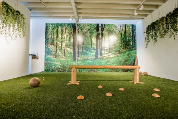 Another view of a biophilic gym. The overall feel is to be immersed in nature, and is achieved with real plants and nature-inspired finishes like a mural depicting a forest and a grass-like carpet.