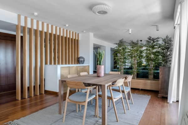 Tall plants visually dividing a dining room area.