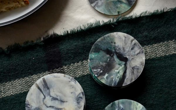 Top view of a table with marbled sustainable coasters made of recycled plastic.