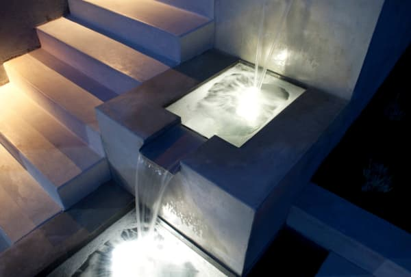 Fountain on the side of a concrete staircase.