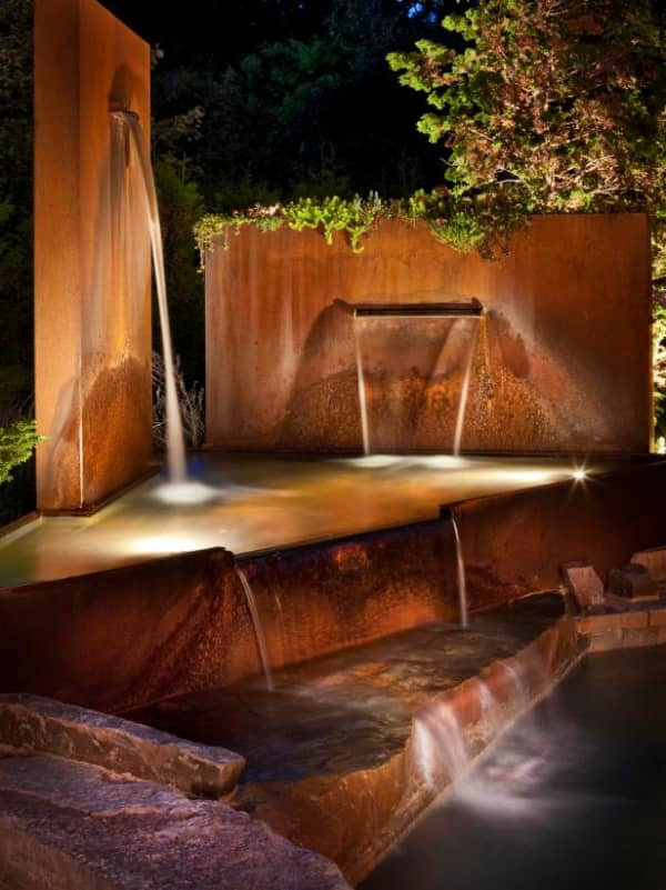 Waterfall coming out of steel panels. Great example of water design feature contributing to a more biophilic design of the space.
