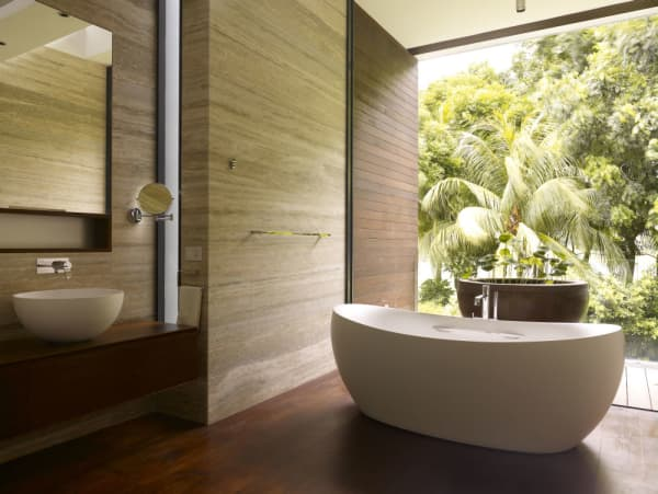 Natural bathroom design with a floor-to-ceiling window looking into the forest.