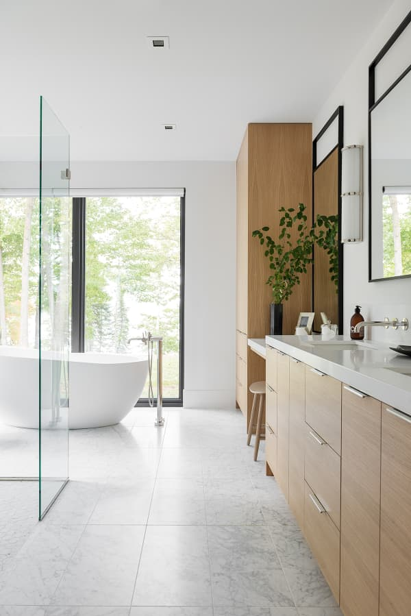 A relaxing bathroom full of sunlight, natural materials and full-height windows looking into nature.
