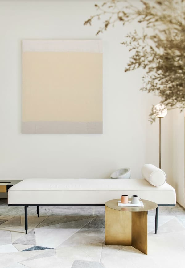 A minimal seating area: white daybed, gold side table and a minimal watercolor art in the background. Perfect setup to enjoy a silent moment.
