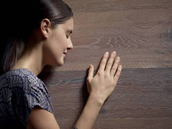A woman touching a wooden surface.