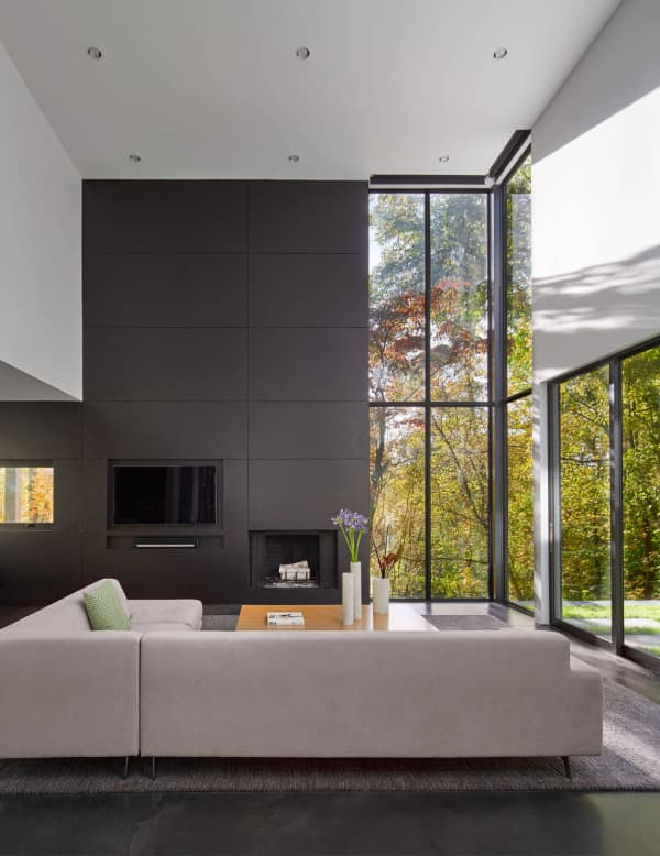 Minimal living room with full-height windows looking into nature. The sofa is placed on the windows.