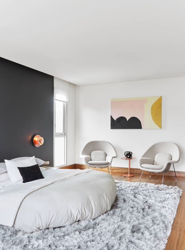 Minimal bedroom in the tones of beige with a pink geometric artwork.