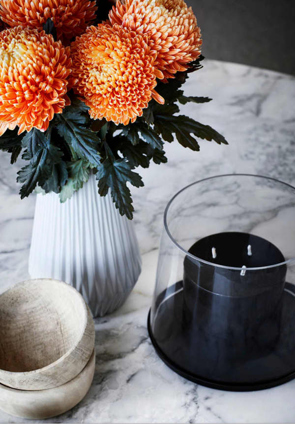 Close-up of a styling with a black candle, wooden bowl and bold orange flowers.