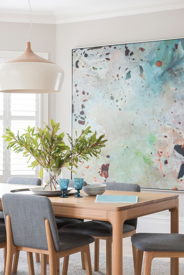 Minimal dining room with a colourful artwork and matching glasses on the table.