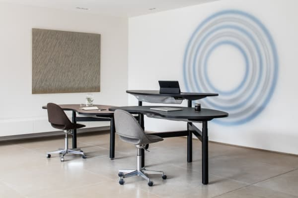 Organic-shaped desks with height adjustment.