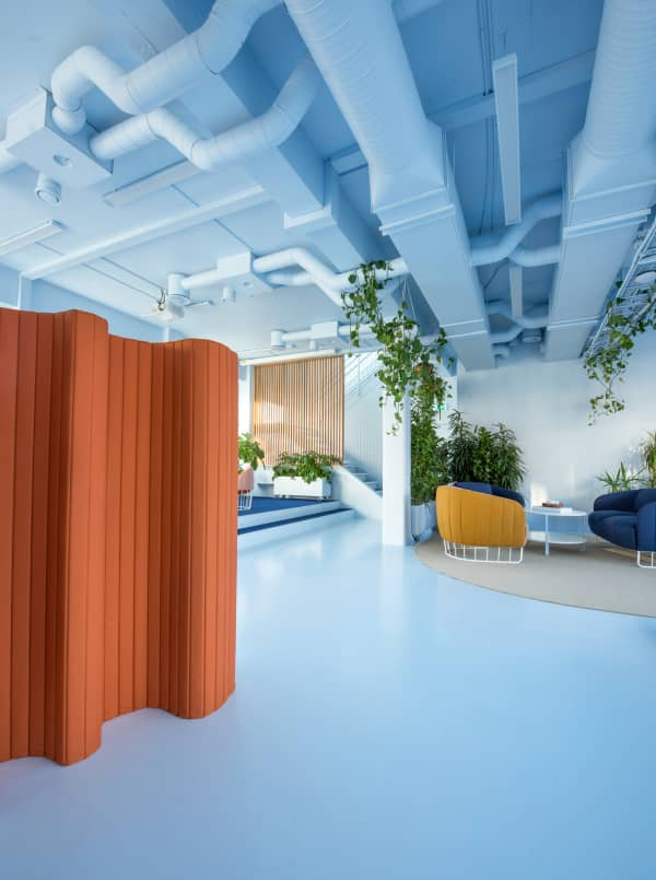 Office open space where the space is divided using acoustic room dividers and wood partitions.
