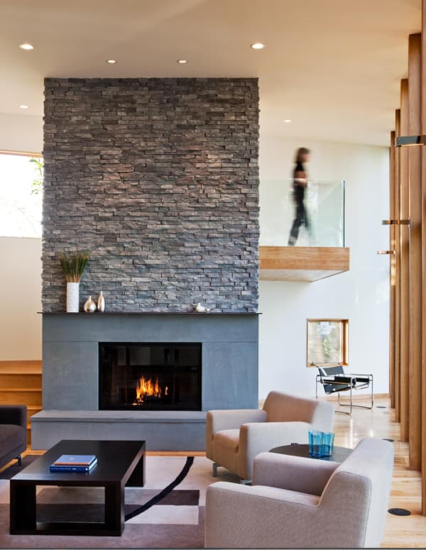 A contemporary living room with huge fireplace cladded in dark stone.
