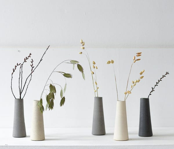 Minimal stone vases with various stems inside.