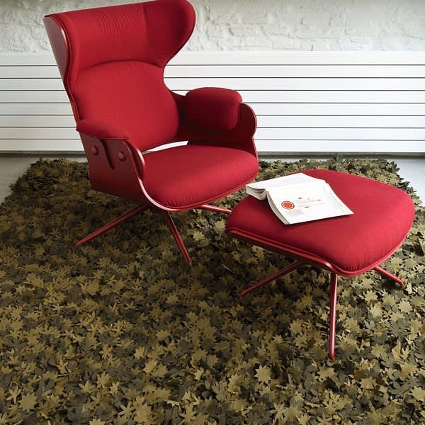 Red armchair on a rug made with little individual wood felt flowers.