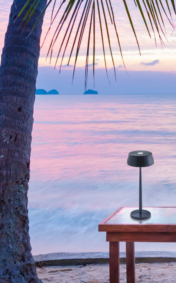 Portable table lamp on a table facing the sea at sunset.