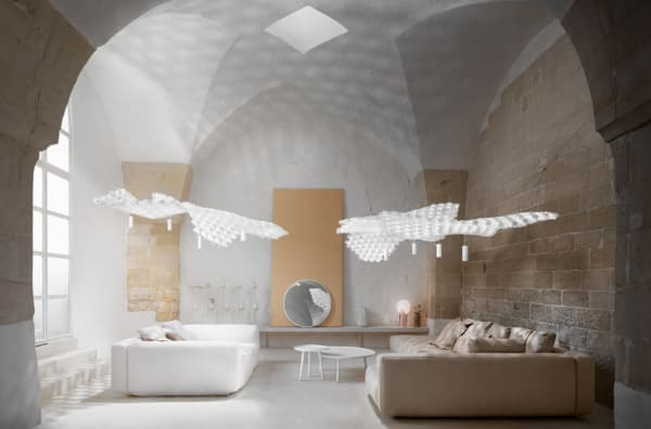 Huge pendant light over a sofa. Its draping look is achieved with individual white modules interlocked.