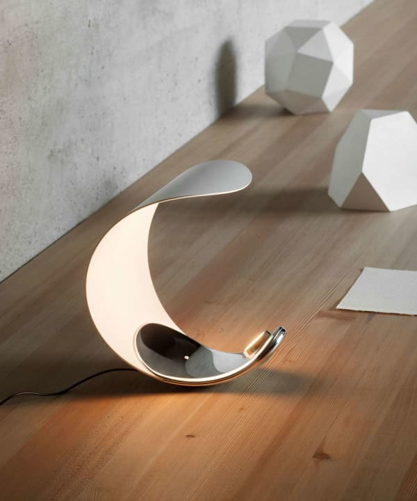 Small table lamp with a curl shape.