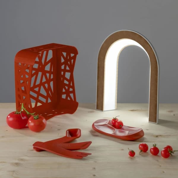 Circular design kitchen utensils: a plate, cutlery and a small crate made out of tomato peels.
