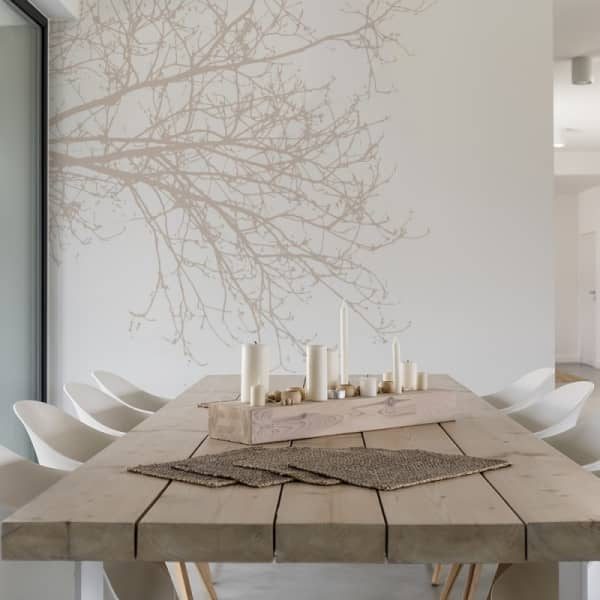 Dining room with a branch wallpaper on the wall.