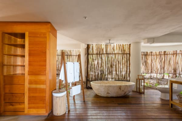 Bathroom of Casa Nalum: the wall is made of bamboo canes that let plenty of natural light in.