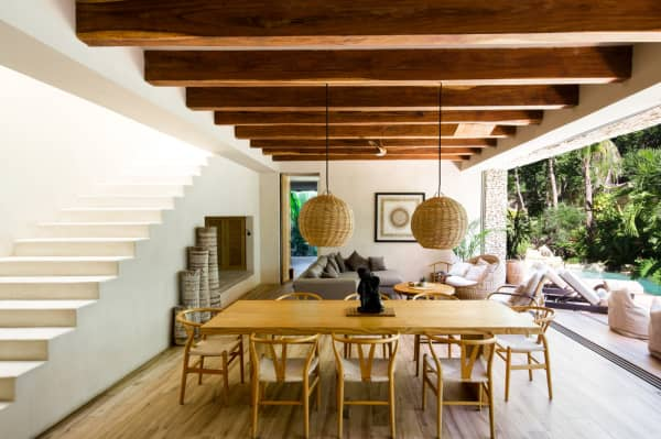 The dining area of Villa Verde, with wooden table and chairs and rattan pendant lights.