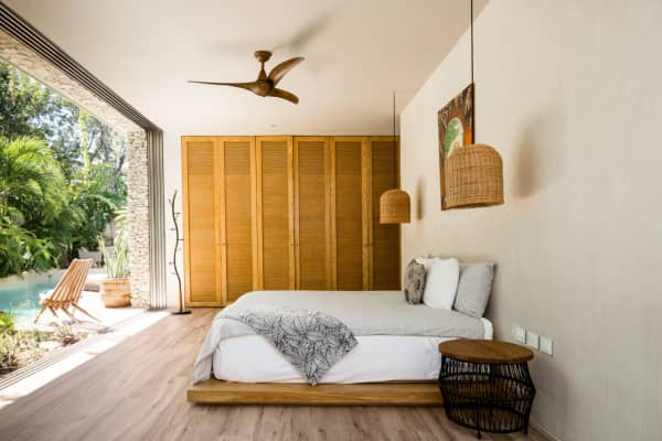 One of the bedrooms of Villa Verde, with a floor-to-ceiling window in front of the bed.