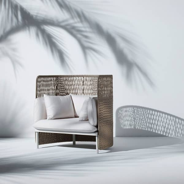 High back white outdoor sofa with a woven back.
