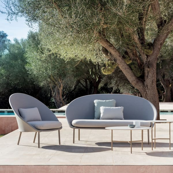 Outdoor sofa and chair with a curved profile.