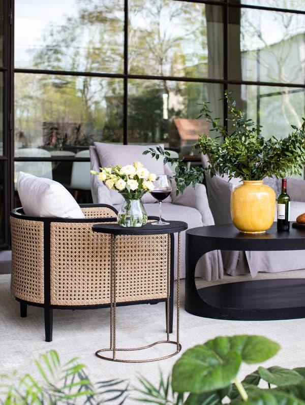 Outdoor seating area with a rattan armchair.