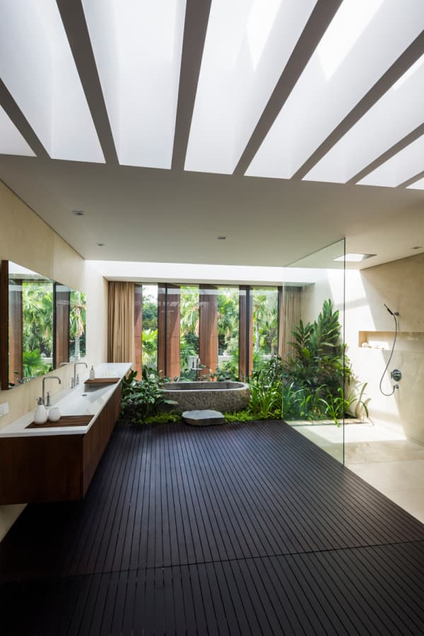 Bathroom facing a huge window with plenty of plants down the bathtub.