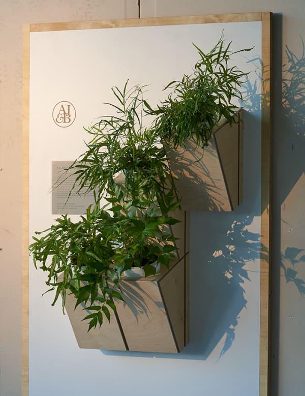 Wood panel housing vases for a vertical garden.