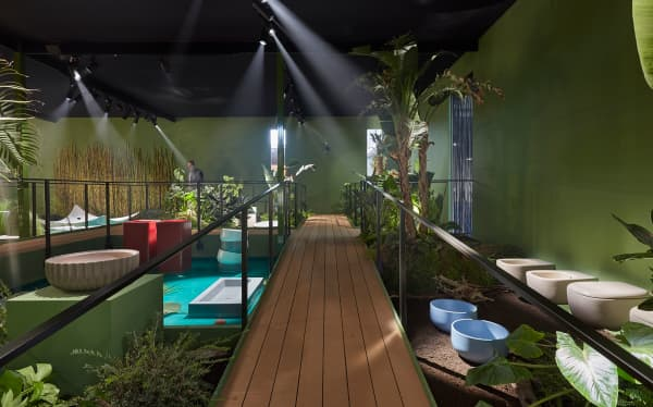Booth designed as a walkway cutting through a jungle where toilets, sinks and bathtubs are displayed.