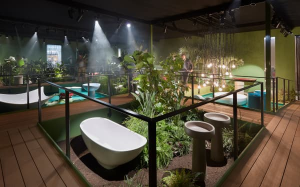 Bathtubs and sinks surrounded by greenery in a jungle oasis inside the booth.
