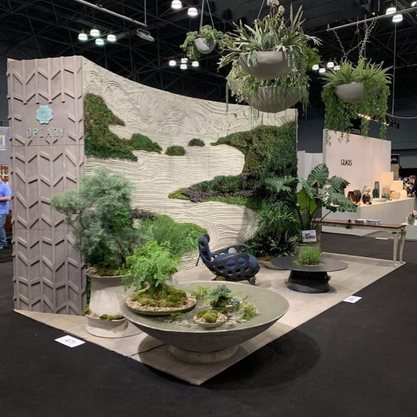 Textured surfaces and lush greenery on a booth wall.