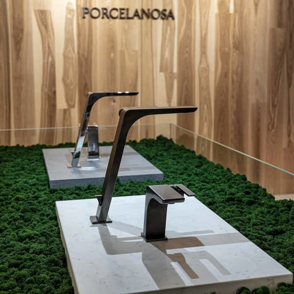 Faucets displayed on a stone slab laid on top of a layer of moss.