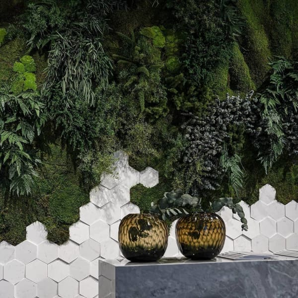 Wall finished with hexagonal tiles on the bottom and a lush vertical garden on the top.