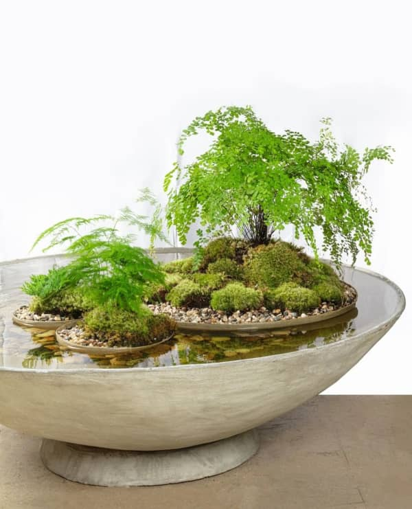 Huge vessel filled with water containing floating smaller vases with plants.