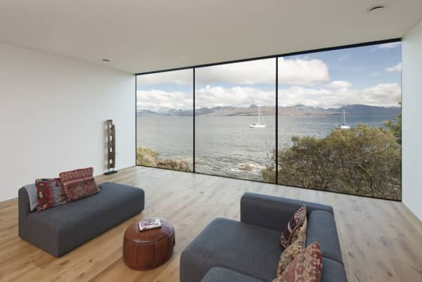 Living room with a full-wall window looking into the sea.