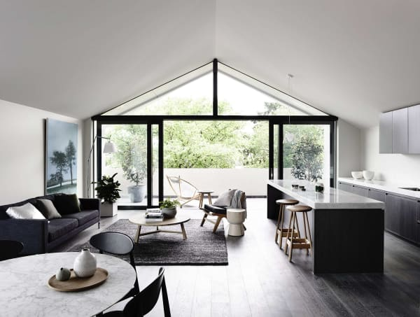 Elongated open plan living area with the back wall fully glazed.